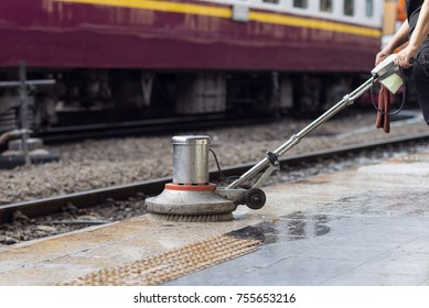 Worker using scrubber machine for cleaning and polishing floor. Cleaning maintenance train at railway station.