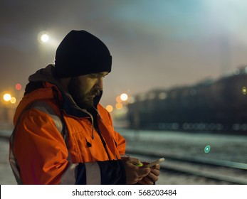 Worker using smartphone in the twilight. Concept of night shift.