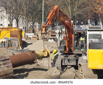 Worker using spanner and hammer to tighten a nut on a steel tube hoisted by a excavator