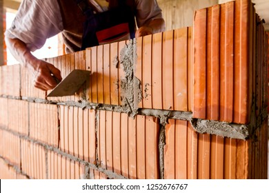 Worker is using spatula, trowel, to scrape off any excess mortar that spreads beyond the wall joint, bricklayer.