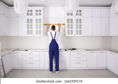 Worker using spirit level while installing new furniture in kitchen
