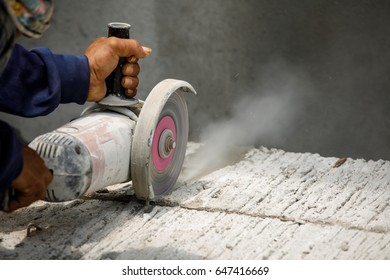 Worker using tool to cut concrete floor