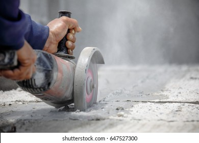 Worker using tool to cut concrete floor with dust in background and copy space in the right