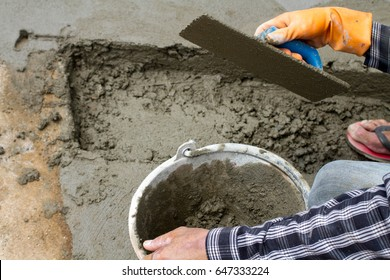 worker  using trowel with orange glove on fresh concrete in construction site