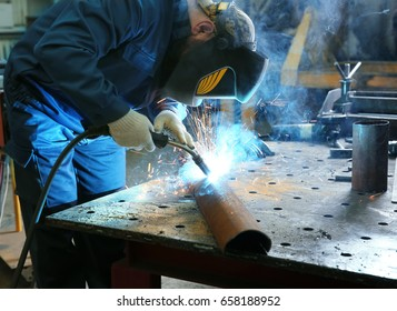 Worker using welding equipment for metalworking in shop