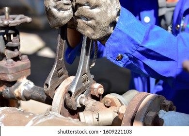 Worker is using the wrenchs to tighten the nut. Technician in blue uniform and leather gloves he is installing valve.