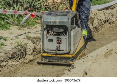 A worker with a vibrating plate in a ditch