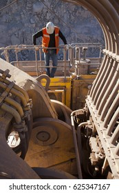 Worker visually inspects an excavator for mining