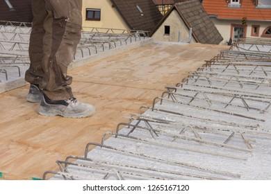 A worker is walking on concrete formwork