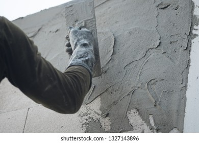 Worker with wall plastering tools renovating house.  Plasterer renovating indoor walls and ceilings with float and plaster.