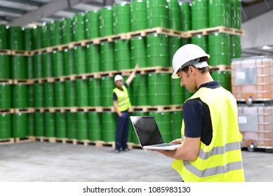 worker in a warehouse with oil barrels checks the stock
