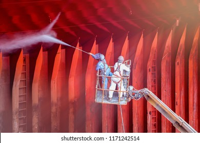 worker wash cleaning in Cargo hold  on sherry picker car wear equipment PPE, safety bell of cargo ship in shipyard