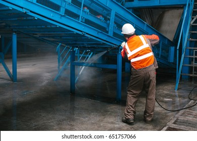 The worker washes the equipment at the waste sorting plant. Waste processing plant. Technological process. Recycling and storage of waste for further disposal.