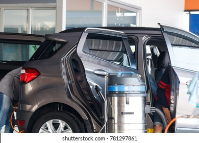 Worker washing car at the car wash shop to clean up dirt and keep the health of the driver and passengers