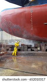 worker washing ship hull at drydock
