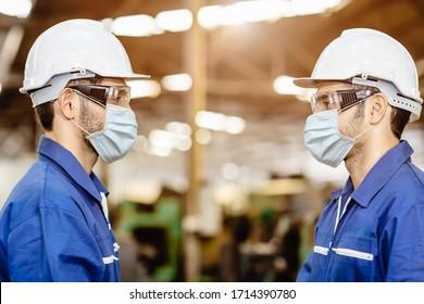 Arbeiter tragen Gesichtsmaske stehen Distanzierung während Gesprächen zusammen Service Arbeiten in der Fabrik, um die Covid-19 Virus-Luftverschmutzung und für gute Gesundheit zu verhindern.