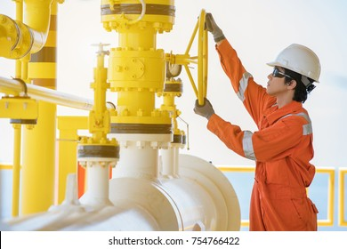 A worker wear helmet gloves safety glass and coverall suite opening valve at oil and gas central processing platform, maintenance and service jot at offshore industry.