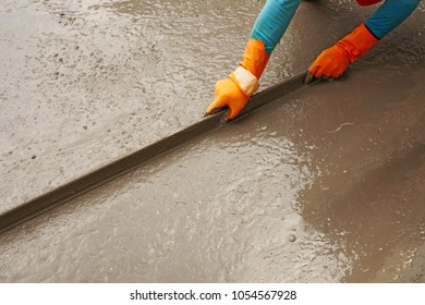 A worker wear the orange gloves spreading and plastering the mortar cement concrete mixed on the ground
