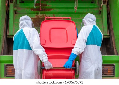 worker wear PPE protective clothing against corona virus of Infectious waste garbage collector truck loading waste and trash bin.