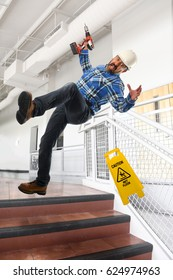 Worker wearing hard hat falling down on stairs inside building