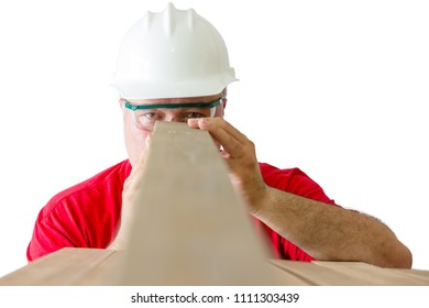 Worker wearing helmet and safety glasses inspecting quality of wooden plank isolated against white background