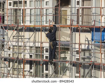 Worker wearing overall and tool belt using hammer to secure a scaffolding tube