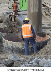 Worker wearing reflective vest and ear protection at a construction site