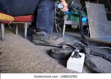 Worker wears safety leather shoes while working for his safety in workplace , cable and unsafe socket on ground.