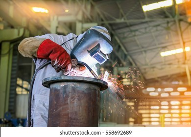 worker welder man welding steel pipe by mig in factory