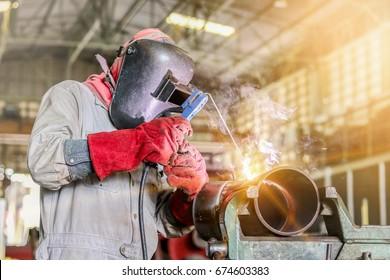 worker welder pipe arc welding at pipe shop in factory