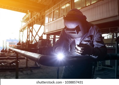 worker welder Tic welding in piping shop in shipyard with office background and dark tone