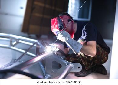 Worker welding aluminum truss using tig welder