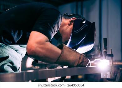 Worker welding aluminum using tig welder