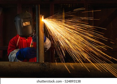 Worker welding construction by MIG welding, Worker welding the steel part by manual