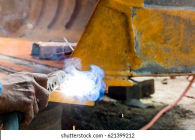 Worker welding the iron for fix wheel loader hand close up.
