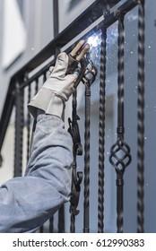 A worker welding metal handrails on the stairs. Ukraine.