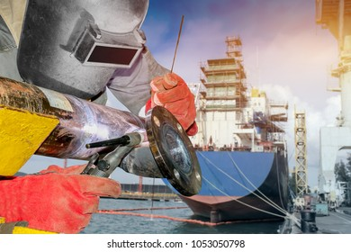 worker welding metal piping using Tig welder and wear equipment protection mask in shipyard