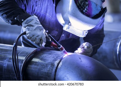 Worker welding metal piping using tig welder/He Work in a Heavy Industry Manufacturer/Industrial worker with protective mask welding inox elements in steel structures manufacture workshop.