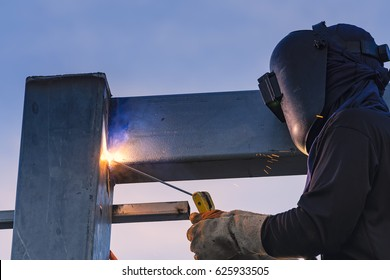 Worker welding parts of stell construction