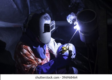 Worker welding pipes structure with welder machine.Craftsman, erecting technical steel Industrial steel welder in factory technical,