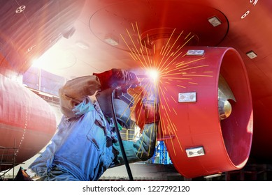 Worker Welding process with Metal steel hull and Proppeler Maintenance, wear equipment protective for safety, a large cargo ship repair in dry dock. shipyard Thailand