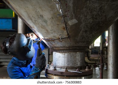 Worker welding repair stainless silo bottom tank using tig welder