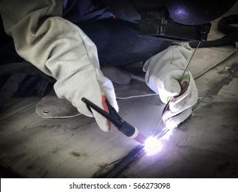 Worker welding stainless tank using tig welder
