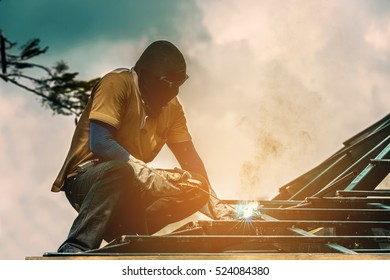 Worker welding the steel to build the roof. (vintage color tone)