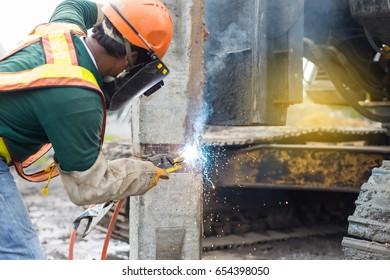 Worker welding steel plate to connect concrete pile, construction work, foundation work.