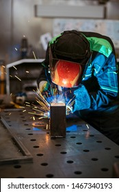 Worker welding two pieces of square tube to form a 90 degree angle
