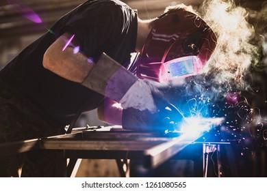 Worker is welding using mig mag welder constructions in the factory