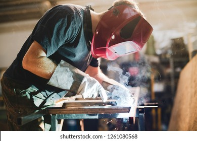 Worker is welding using mig mag welder constructions in the factory