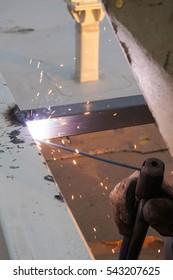 Worker welds a steel box profile