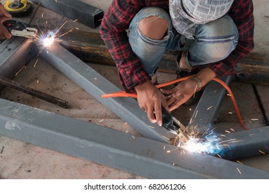 Worker while doing a welding with arc welder.